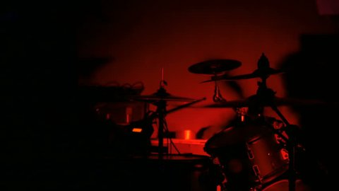Unrecognizable male drummer silhouette playing the drums. Red light, low key. Entertainment and art concept