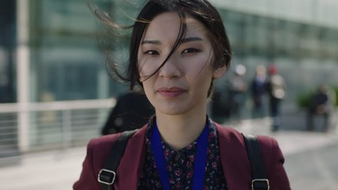 close up portrait of young asian woman looking to camera hair blowing in wind corporate campus education