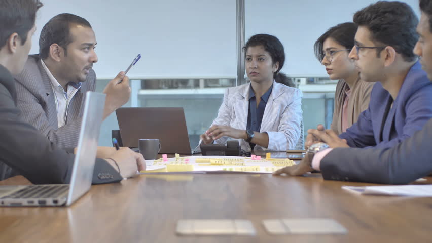 A business team of mixed gender and ethnicity taking an important and critical financial decision in a conference meeting. A serious and focused creative office workers interacting on upcoming project