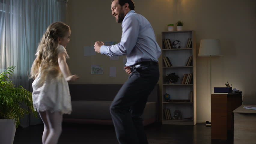 Little daughter and father enjoying dance at home, having fun together, party