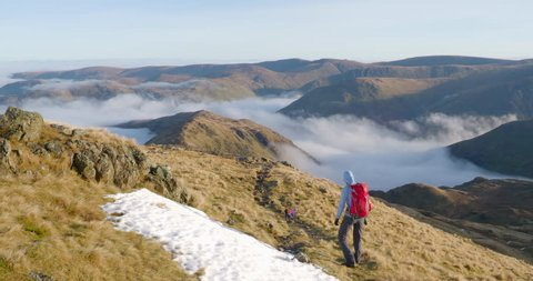 A hiker and their dog descending Hart Crag by Hartsop Above How with a cloud inversion below in the English Lake District, UK.