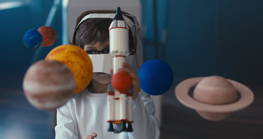 CU Cute little boy wearing cardboard astronaut helmet flying toy rocket through planets, exploring deep space. 4K UHD 60 FPS SLOW MO