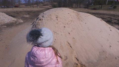 Little girl on sand pile