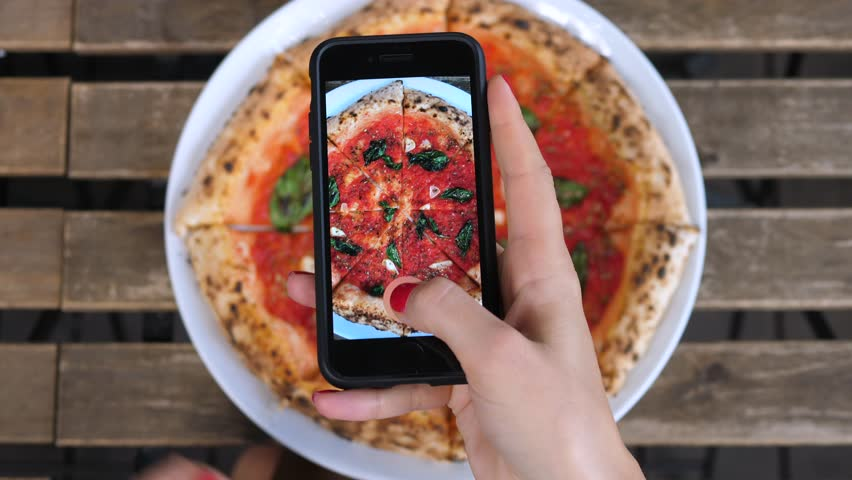Technology, People And Food Porn Concept. Taking Picture Of Pizza With Smartphone.