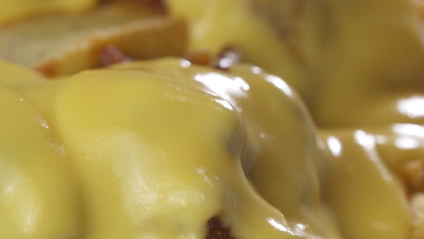 Macro closeup chef putting melted cheese on top of the french fries chips with chilli con carne sauce - video in slow motion