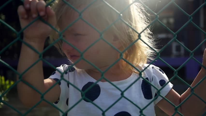 A little blond girl, standing behind a netting fence, holds her hands. slow motion. 1920x1080. full hd