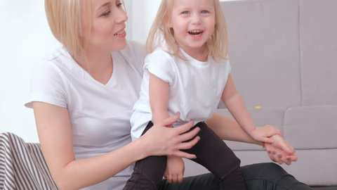 Attractive young blond mom and her charming daughter playing together with pink balloon. Closeup portrait.