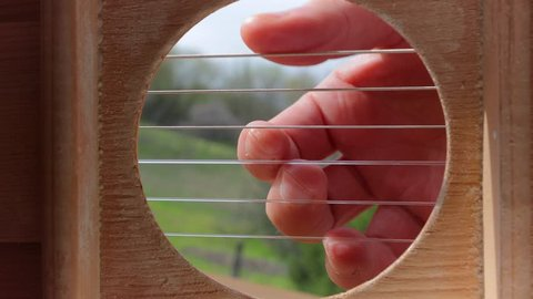 Playing acoustic guitar viewed from the inside, weird perspective