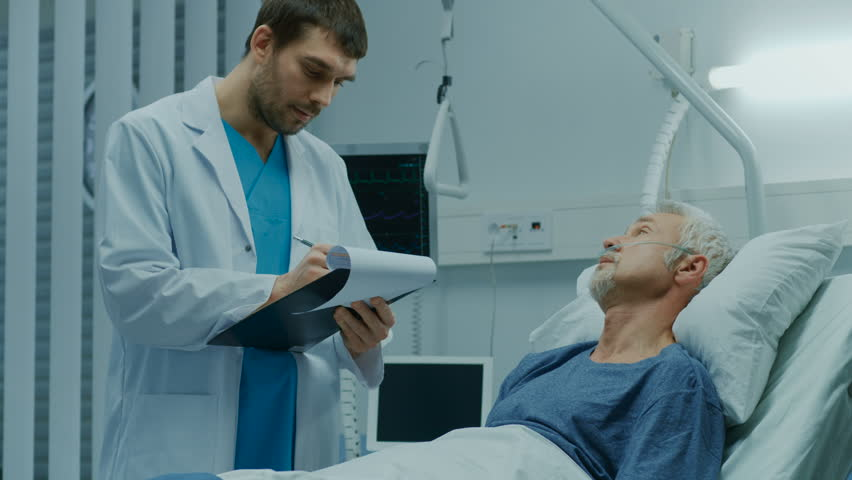 In the Hospital, Recovering Senior Patient Lying in Bed Talks with a Friendly Doctor. Professional Doctor Asks Patient Vital Questions in the Modern Geriatrics Ward. | Shutterstock HD Video #1009728617