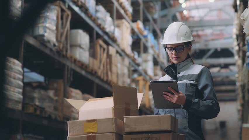 A woman in a warehouse in a white helmet and gray uniform opens a cardboard box, looks at the goods and makes an inventory. Merchandiser recounts the item in the box and makes notes on the tablet.