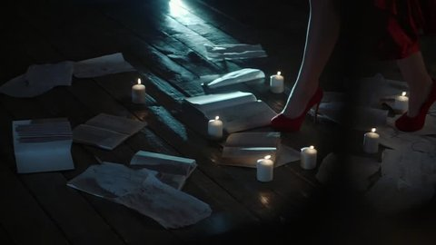 A close shot at the woman's feet, the lady passes by scattered books and  burning candles on the floor, she is dressed in high scarlet shoes