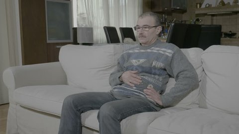 Sick retired man in pain dealing with acute stomachache result of gastric illness sitting on couch at home