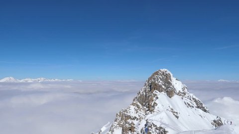 A breathtaking view opens from the summit of mountain. It's a perfect day to spend skiing. Panorama from left to right. Lots of clouds are above mountain peaks on background. 4k, 3840x2160