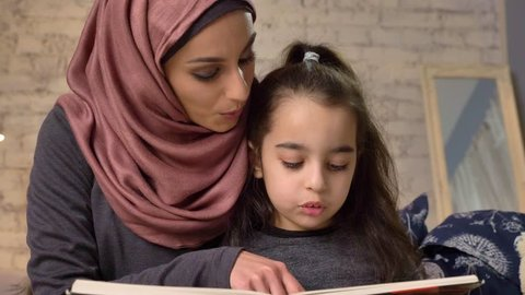 Young woman in hijab sits on sofa with her daughter and teaches her how to read, book, happy family concept, close up 50 fps
