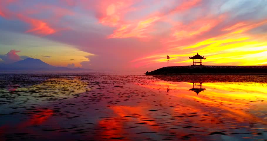 Traversing View Asian Pagoda On Ocean Coast During Tropical Sunrise With Water Reflecting Orange, Red And Yellow Sunlight - Sanur Beach, Indonesia