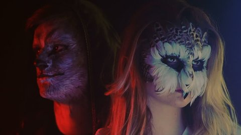 Close-up Plan, Owl Girl and Wolf Boy in the Black Hood Look in Different Sides in the Smoky Studio