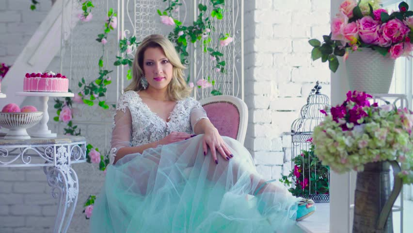 Beautiful model in peignoir sitting in a chair against white brick wall with flowers.