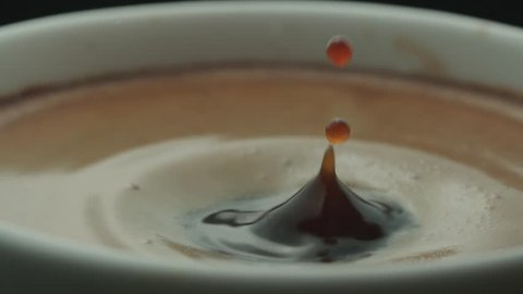 last drop of espresso falls into the filled Cup from the coffee machine in slow motion