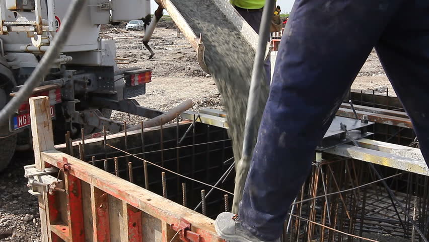 Zrenjanin, Vojvodina, Serbia - April 30, 2015: Workers at building site are pouring concrete in mold from mixer truck. | Shutterstock HD Video #1009802627