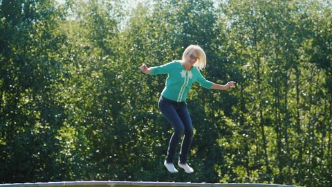 A middle-aged woman high up on a trampoline. Active lifestyle. Slow motion video