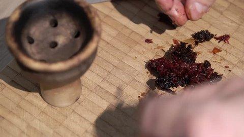 Man preparing shisha tobacco for hookah bowl smoking