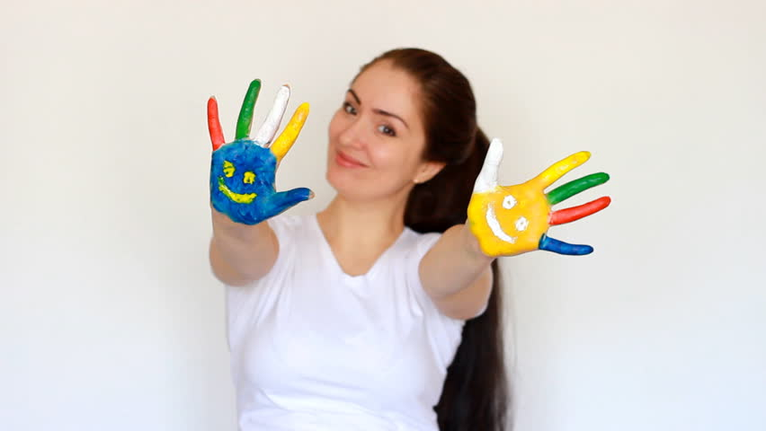 Smile. Smiles. Concept education, creativity, art and painting. Portrait student girl smiling girl showing painted multicolored hands with smiles on a light white background | Shutterstock HD Video #1009823897