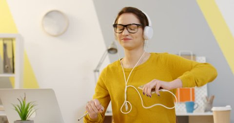 Young joyful woman in a yellow sweater, glasses and white headphones listening to the music on her smartphone and dancing while sitting at the table in the office. Indoors