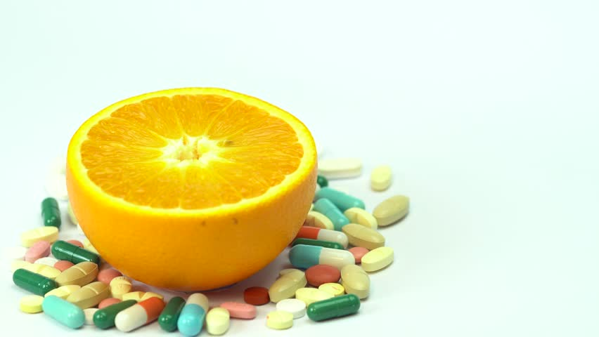 Close up of orange fruit and pills isolated - vitamin concept | Shutterstock HD Video #1009841837