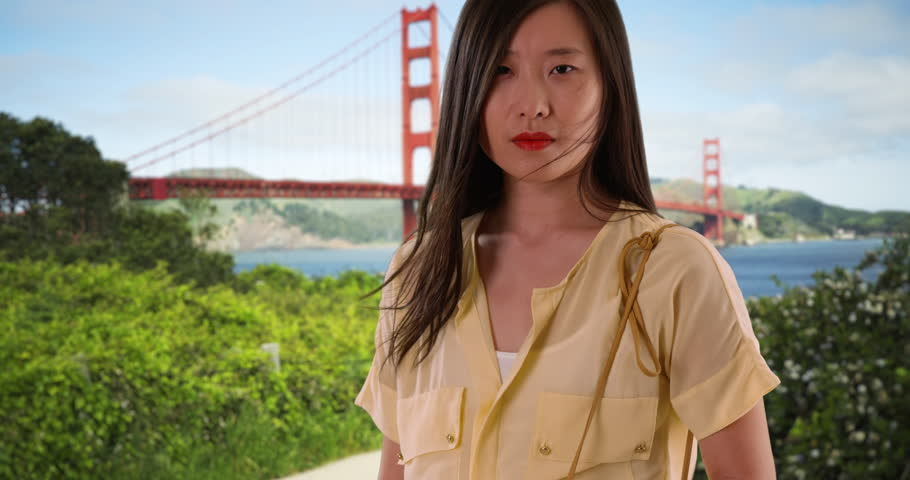Portrait of Chinese woman standing in front of Golden Gate Bridge and looking at camera. Asian female millennial tourist with hair blowing in the wind visiting San Francisco. 4k