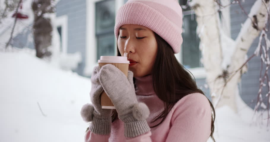 6762e4db7 Lovely millennial woman staying warm with hot beverage and wearing mittens  and beanie in snow covered town. Close up of cute Asian woman holding cup  in ...