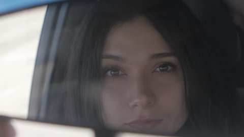 Close up Young beautiful woman looking in rear view mirror while sitting in car