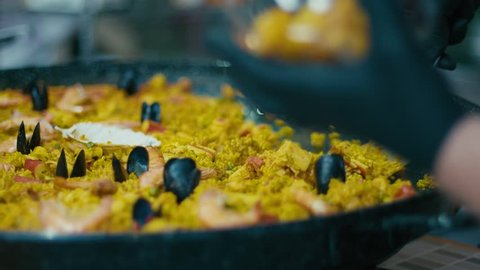 Cooking a large mixed Spanish paella dish. Rice, saffron, shrimps, mussels