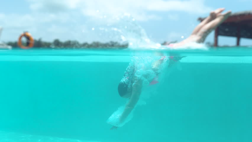SLOW MOTION, HALF UNDERWATER: Active young woman dives into empty pool and splashes glassy water. Caucasian girl jumps head-first into refreshing pool during relaxing stay in tropical hotel resort.