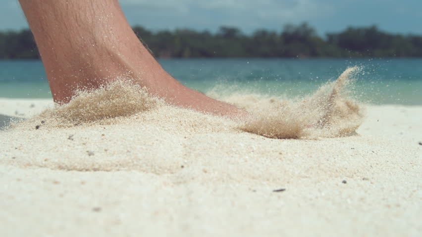 SLOW MOTION, CLOSE UP, LOW ANGLE: Unknown man steps barefoot into scorching hot white sand on idyllic exotic beach. Male foot steps into sand and makes grains of sand fly around calm tropical coast.