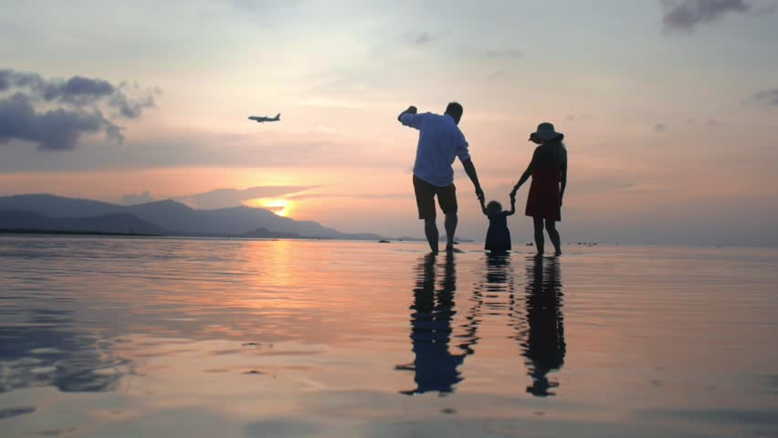 Parents show child how the airplane taking off. Family standing on the beach at sunset, hold daughter s hands and talking. Slow-motion, view from the bottom.