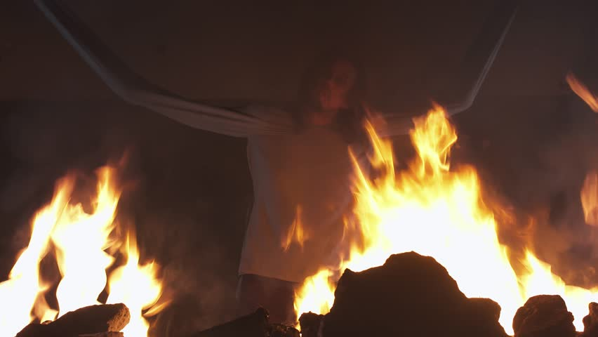 Crazy long haired caucasian man with straitjacket sleeves tied to ceiling struggling in burning abandoned building