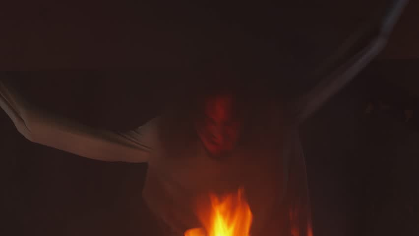 Mad long haired caucasian man with straitjacket sleeves tied to ceiling struggling in burning abandoned building