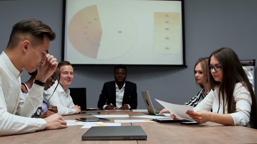 A group of creative multi-ethnic managers disassemble at the meeting of the board of directors in the conference hall the graphs of profit for the last year in the firm. The boss of an African   Shutterstock HD Video #1009936037