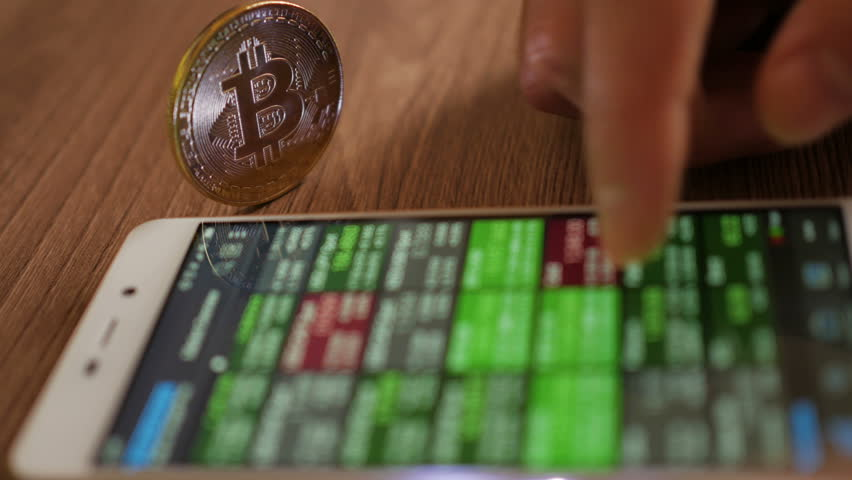 Bitcoin is a worldwide cryptocurrency and digital payment system. Businessman reading financial news. Stock market, trading online, trader working with smartphone on stockmarket trading floor. 4K UHD | Shutterstock HD Video #1009950857