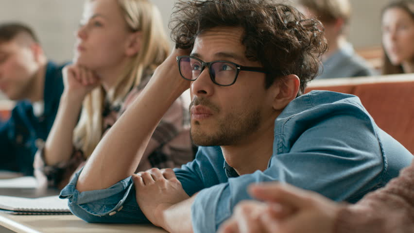 Bored Male Student Listening Lecture at the University. Tired, Exhausted and Overworked Young Male.  Shot on RED EPIC-W 8K Helium Cinema Camera.