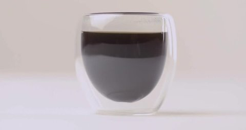 Pouring milk in cup with coffee on white background