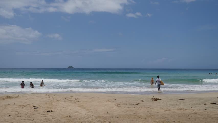 People in sea on tropical beach of Nagtabon Beach   Shutterstock HD Video #1009958477