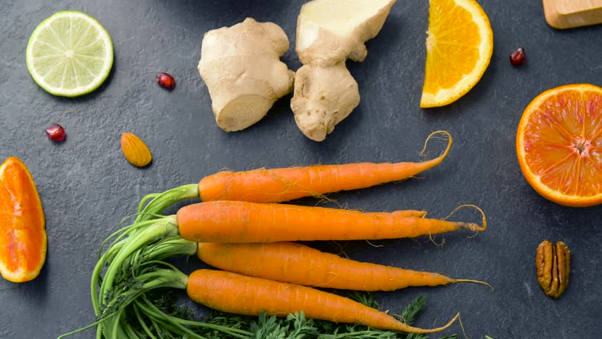 food and  healthy eating concept - close up of carrot, ginger root, orange, lemon and nuts on table top