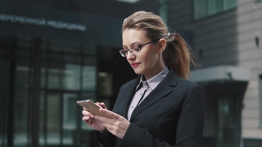 The girl in a business suit sends a texting on mobile phone. the wind in your hair   Shutterstock HD Video #1009964477