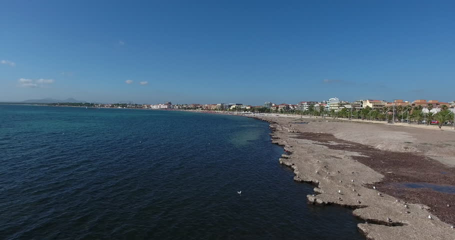 ALGHERO, SARDINIA, ITALY – JULY 2016 : Aerial shot over Alghero beach on a beautiful day with people and cityscape in view