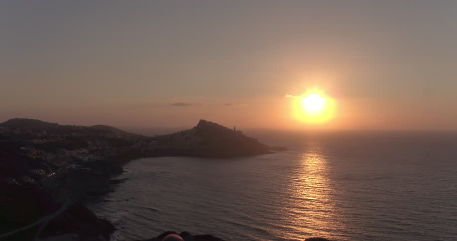 SARDINIA, ITALY – JULY 2016 : Video shot of a girl enjoying beautiful view of Castelsardo landscape during sunset with sea in view | Shutterstock HD Video #1009990277