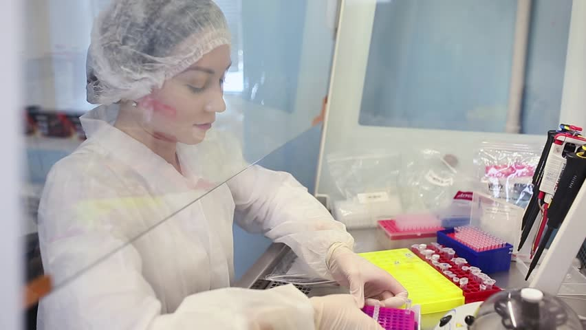 Close-up of female technician with multipipette and in genetic laboratory doing PCR research. Young woman is genetics scientist and she loads saliva samples for DNA amplification