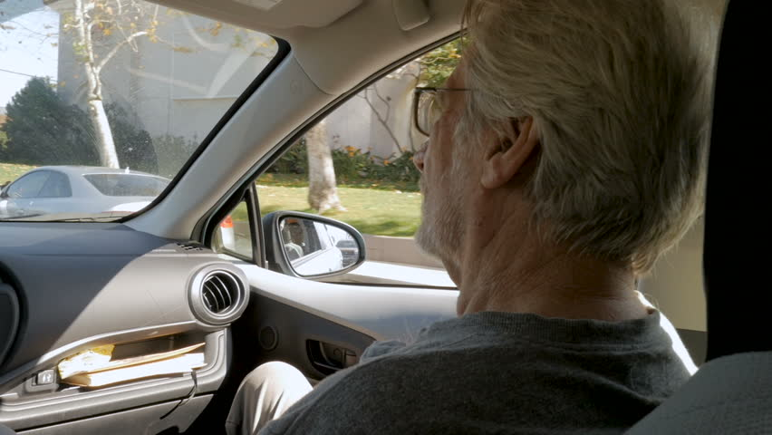 Los Angeles, UNITED STATES - CIRCA FEBRUARY 2018 - Elderly senior man sitting in the passenger seat of a car being driven through a suburban part of the city in slow motion   Shutterstock HD Video #1010013527