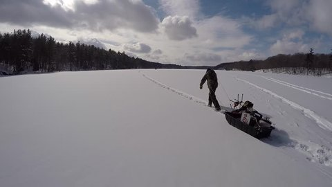 man pulls camping gear in sled to hut on the frozen lake gimbal follow cam