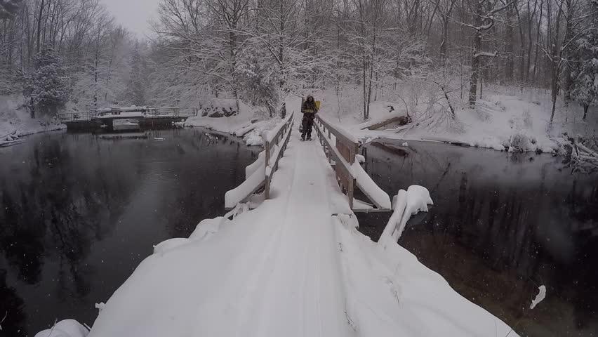 pov walking towards man in camo on bridge slow motion while it snows